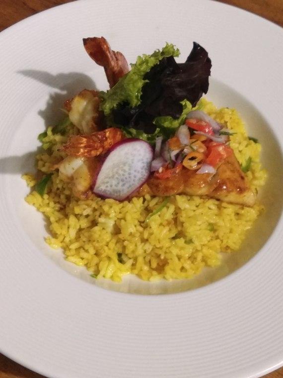 Nasi goreng bali di sajikan dengan udang dan ikan kakap bakar serta sambal matah dan lalapan